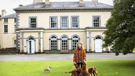 Artist Andrea Jameson outisde her magnificent home, Tourin, on the banks of the river Blackwater in Cappoquin, Co Waterford. The house, which is on 360 acres, was built in 1840 by her ancestors the Musgraves, and was completely restored by her parents in the 1950s. Andrea and her sisters decided to paint the exterior a soft ochre 15 years ago. The three red setters belong to her sister Kristin, who trains them. Andrea's own dog, Sandy, is off to the side. Photo: Tony Gavin