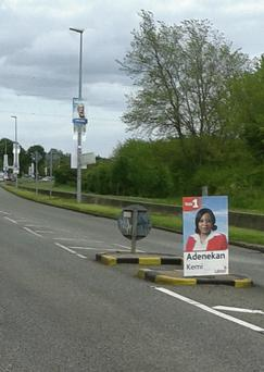 An election poster placed at a traffic crossing island.