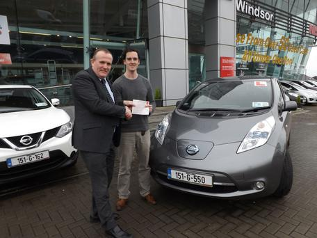 Success: David, on right, holding his certificate of competency with Windsor Motors dealer principal Michael Butler beside the Nissan Leaf.
