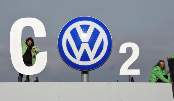 A Greenpeace activist adds a pointed message to a Volkswagen sign at the company's plant in Wolfsburg, Germany, Photo: Fabian Bimmer/Reuters