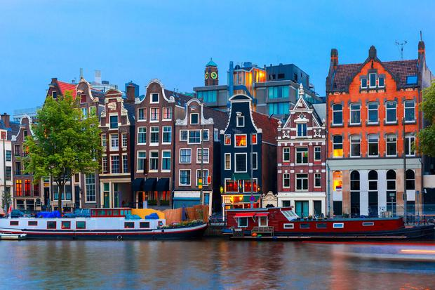 Night-time view of Amsterdam's typical canal side houses with modern architecture behind them. Photo: iStock/PA.