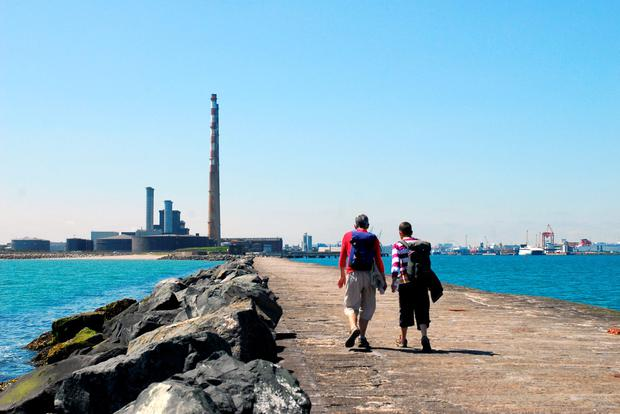 Two walkers enjoy a stroll along the Great South Wall, which extends some 2km into Dublin Bay. In the near distance are the towers of the Pigeon House power station, a Dublin icon.