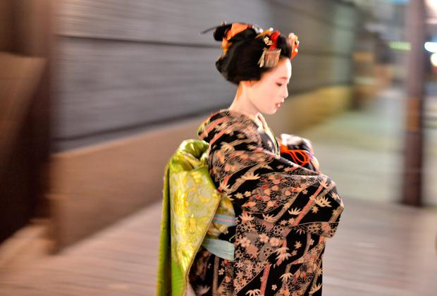 A maiko, or apprentice geisha, walks between teahouses in Gion, Kyoto