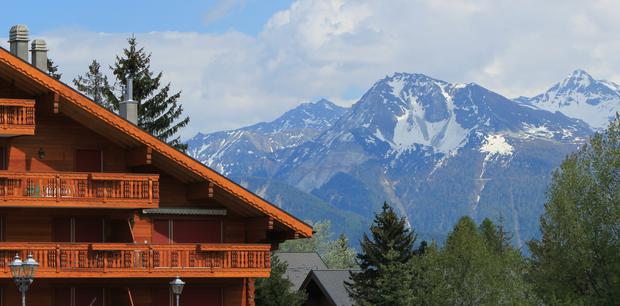 Swiss chalet and Alps mountains in summer at Crans-Montana, Switzerland