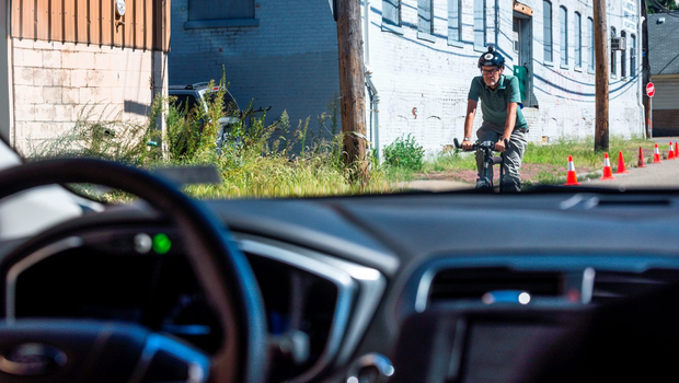 A biker passes a pilot model of the Uber self-driving car on September 13, 2016 in Pittsburgh, Pennsylvania. Photo: ANGELO MERENDINO/AFP/Getty Images