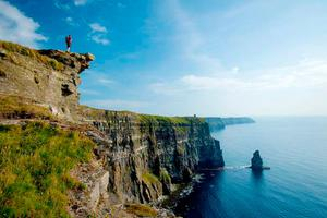 Hiker dwarfed by the Cliffs of Moher, with O'Brien's Tower in the distance. Photo: Gareth McCormack, from Ireland's Wild Atlantic Way –A Walking Guide by Helen Fairbairn (The Collins Press, 2016)