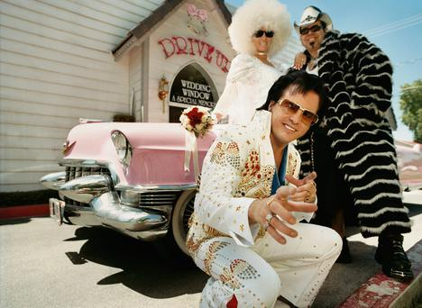 An Elvis impersonator outside a wedding chapel