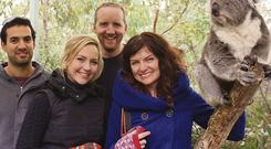 Thomas, centre, smiles for a koala kodak moment in Cleland wildlife park