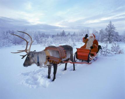 Sleigh ride: Santa waves as he heads off for a trip on his sleigh, pulled by one of his many reindeer