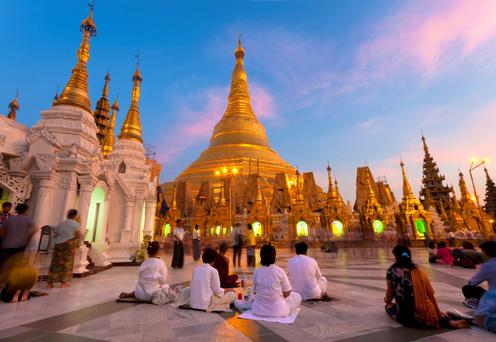 The Shwedagon Pagoda in Yangon at dusk with Buddhist worshippers praying. The huge pagoda can be seen from all over Yangon.