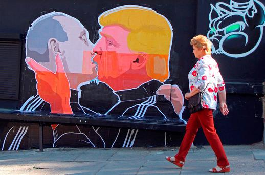 A woman walks past a mural on a restaurant wall depicting US Presidential hopeful Donald Trump and Russian President Vladimir Putin greeting each other with a kiss in the Lithuanian capital Vilnius. Photo: PETRAS MALUKAS/AFP/Getty Images