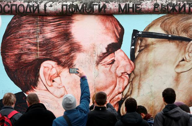 BERLIN, GERMANY, 2009: Visitors photograph graffiti by Dmitri Vrubel featuring Leonid Brezhnev and Erich Honecker kissing under the words, in Russian, 'Pomogi mne vyzhit' sredi etoy smertnoy lyubvi,' or 'My God, Help Me to Survive This Deadly Love,' during celebrations for the 25th anniversary of the fall of the Wall. Photo by Adam Berry/Getty Images)