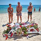 Holidaymakers view flowers left on Marhaba beach where 38 people were killed in a terrorist attack last June in Sousse, Tunisia