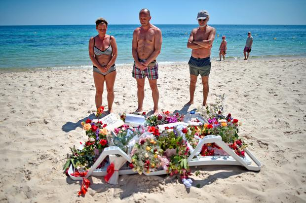 Holidaymakers view flowers left on Marhaba beach where 38 people were killed in a terrorist attack in June 2015 in Sousse, Tunisia