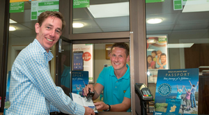 Ryan Tubridy is pictured in the Buncrana Post Office getting his Wild Atlantic Way passport stamped after visiting Inishowen by Postmaster, Christian McGinley. Photo: Clive Wasson