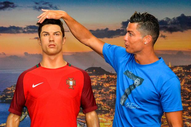 Cristiano Ronaldo poses next to a wax statue of himself during a visit to the CR7 museum at Funchal, Madeira. Photo: JOANA SOUSA/AFP/Getty Images