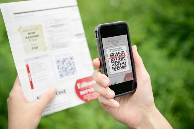 Scanning advertising with QR code on a mobile. Photo: Deposit