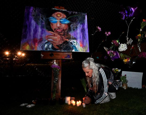 Fans light candles outside Paisley Park in Minneapolis, Minnesota, on April 21, 2016. Photo: MARK RALSTON/AFP/Getty Images