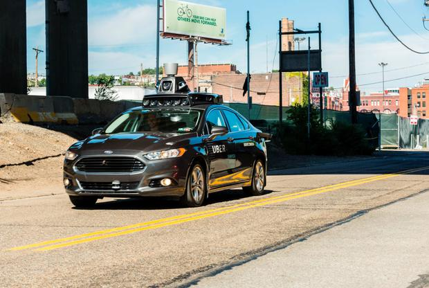 A passenger look on as he rides in a pilot model of an Uber self-driving car on September 13, 2016 in Pittsburgh, Pennsylvania. Photo: ANGELO MERENDINO/AFP/Getty Images