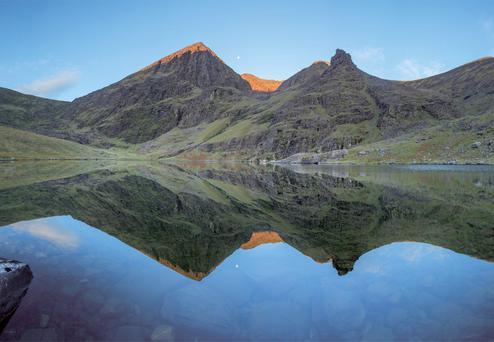 The first rays of dawn warm the summits of Carrauntoohil and Beenkeragh, reflected in the still waters of Lough Gouragh, Co. Kerry. Taken from 'The Mountains of Ireland' by Gareth McCormack (The Collins Press, 2016)