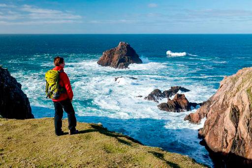 A walker beside the narrow chasm that separates Illandavuck from Erris Head. Photo: Gareth McCormack, from Ireland's Wild Atlantic Way –A Walking Guide by Helen Fairbairn (The Collins Press, 2016)