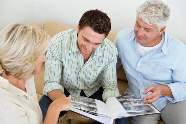 A family looking through a photo album. PA Photo/thinkstockphotos.