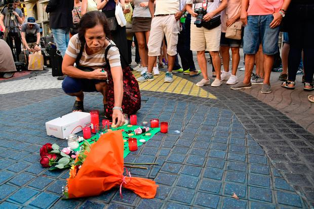 A woman displays a candle next to first flowers and a message to the victims on August 18, 2017 on the spot where yesterday a van ploughed into the crowd, killing 13 persons and injuring over 100 on the Rambla boulevard in Barcelona. Photo: JAVIER SORIANO/AFP/Getty Images