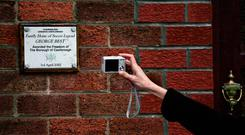 Belfast: A woman takes a pictures of a plaque at George Best's father's home in Belfast in December 2005. Best died on November 25, 2005. Photo: NICOLAS ASFOURI/AFP/Getty Images