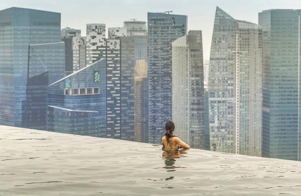 woman relaxing in infinity pool over city.