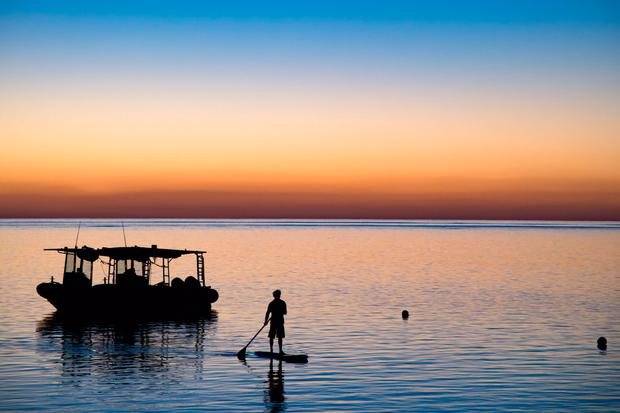 A paddle boarder at sunset on Heron Island, Australia. PA Photo/Sarah Marshall.