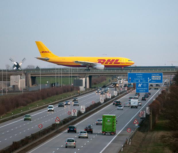 A DHL aircraft crosses the Autobahn. Photo: Bodo Schulz\ullstein bild via Getty Images