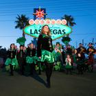 A dancer from Sharon Lynn Academy of Irish Dance performs as local officials, business people, pipers, showgirls, and employees of Ri Ra Irish Pub pose in front of the