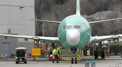 A worker stands near a Boeing 737 MAX 8 airplane parked at Boeing Co.'s Renton Assembly Plant (Ted S Warren/AP)