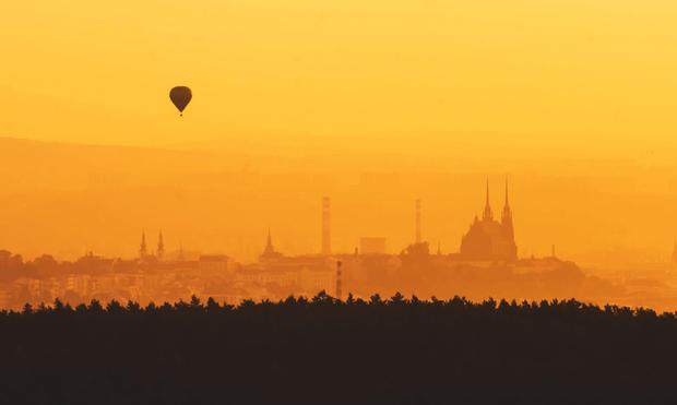 A balloon flies over the city of Brno at sunset, with the cathedral seen in silhouette
