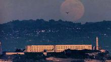 CLASSIC ROCK: A full moon rises over Alcatraz Island in the San Francisco Bay and the Berkeley Hills in California. An audio tour of the island's former prison includes inmates' testimonies