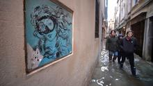 """People walk in a flooded street in Venice, during """"acqua alta"""", or high water, of over five feet, on November 17, 2019. Photo by FILIPPO MONTEFORTE/AFP via Getty Images"""