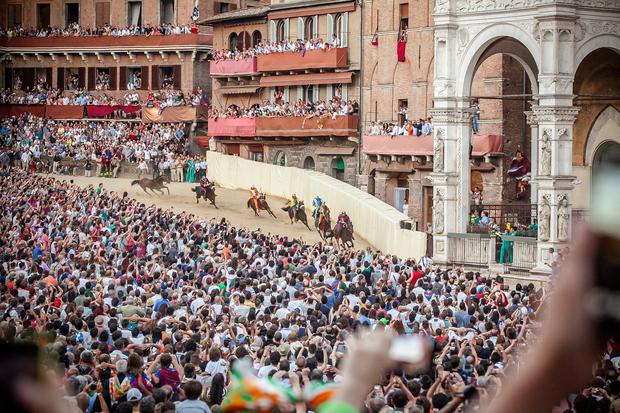 The Palio di Siena, held twice a year. Ten horses and riders, bareback and dressed in the appropriate colours, represent ten of the seventeen contrade, or city wards. Photo by Mario Llorca/Corbis via Getty Images