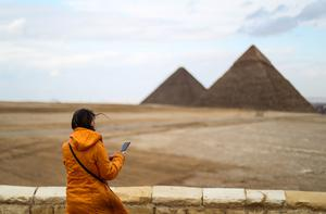 A tourist looks at her phone while standing at an overlook by the (L to R) Great Pyramid of Khufu (Cheops) and Khafre (Chephren) at the Giza pyramids  in Egypt on March 13, 2020. Photo: Mohamed el-Shahed / AFP