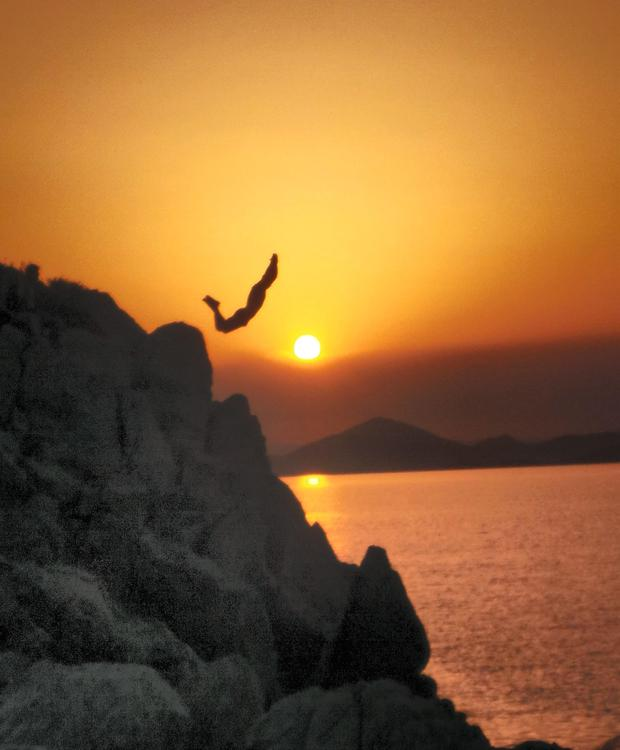 Irish skipper Max cliff dives at sunset during The Yacht Week in Greece