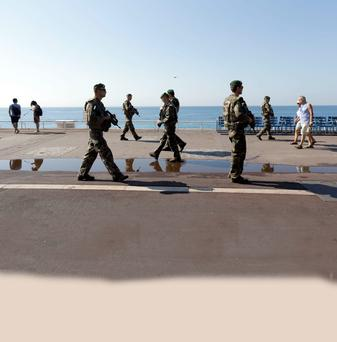 After the slaughter: Troops patrol Promenade des Anglais in Nice.