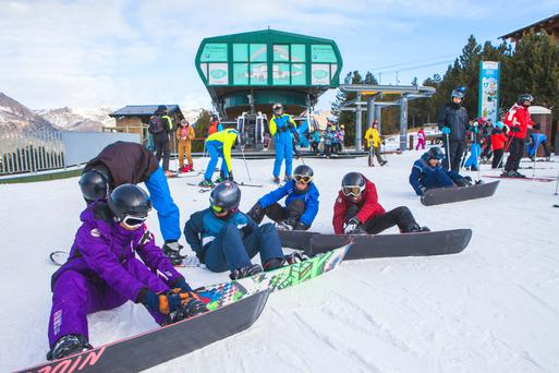 Snowboarders check their bindings on the slopes of Grandvalira