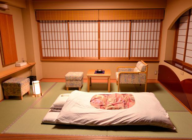 A futon is laid out for the evening at a ryokan, or traditional Japanese Inn. Omotenashi no Yado Keizankaku, outside Kyoto.