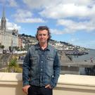 The bells: Nick, above, enjoys the sights of Cobh, with the famous cathedral in the background.