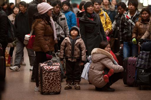 Chinese Lunar New Year travellers check train times at a station in Beijing on January 4, 2012.