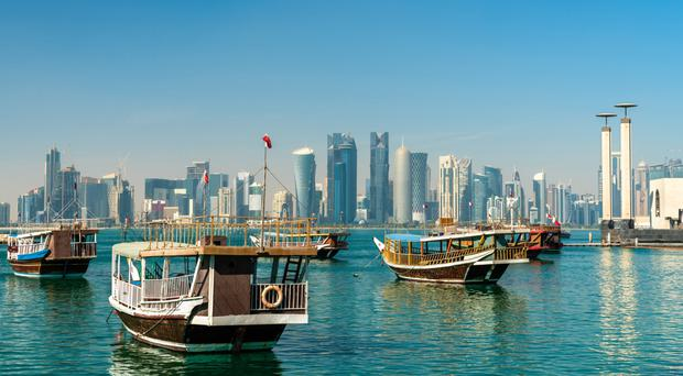 Traditional dhows afloat in the bay facing the ultra-modern skyline of Doha