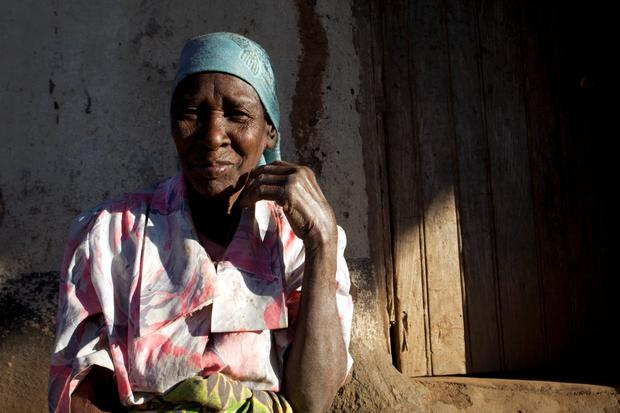A woman sits outside her home in Lilongwe