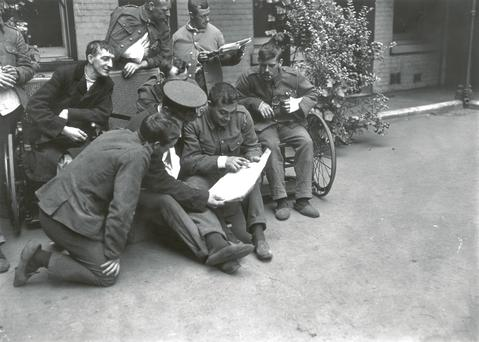 Wounded soldiers in a London hospital gather round to read the news from the front lines in 1914.