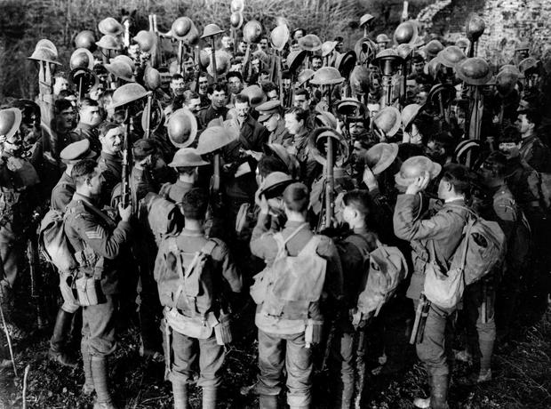 The First Battalion of Irish Guards hold aloft their helmets in France as they hear the news of the armistice. Photo: Hulton Archive/Getty Images