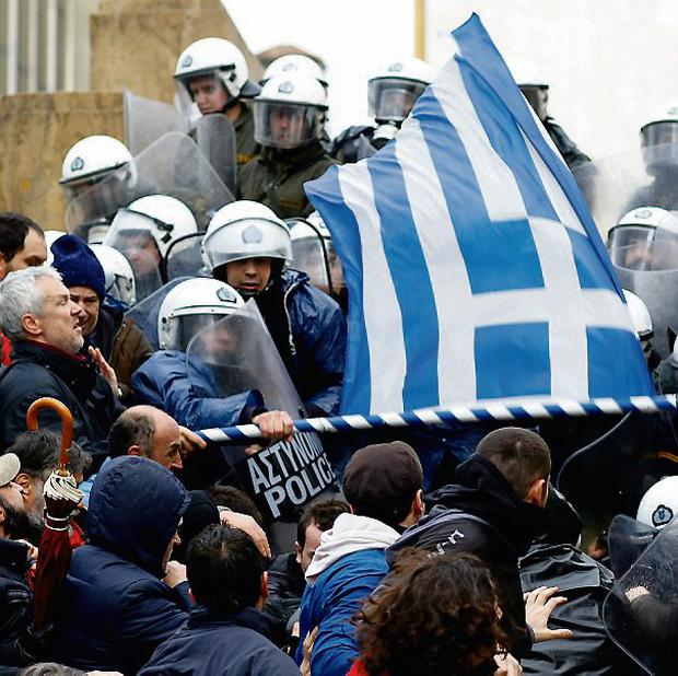 Protests In Athens As Government Works To Secure Bailout...Riot policemen clash with protesters trying to reach the entrance of the Greek Parliament building during a 24-hour general strike in Athens, Greece, on Tuesday, Feb. 7, 2012. Greece's government and international creditors are working on the final draft of an agreement on budget and structural measures needed to free up a second aid package, a Greek official said. Photographer: Kostas Tsironis/Bloomberg via Getty Images...I