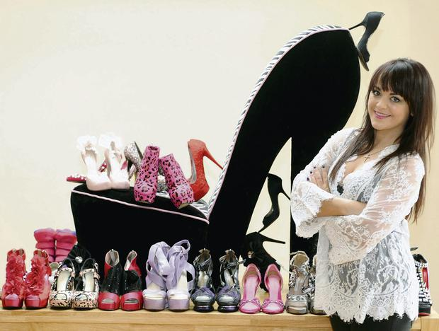 Ali Murray, with part of her shoe collection, and her chair in the shape of a shoe.